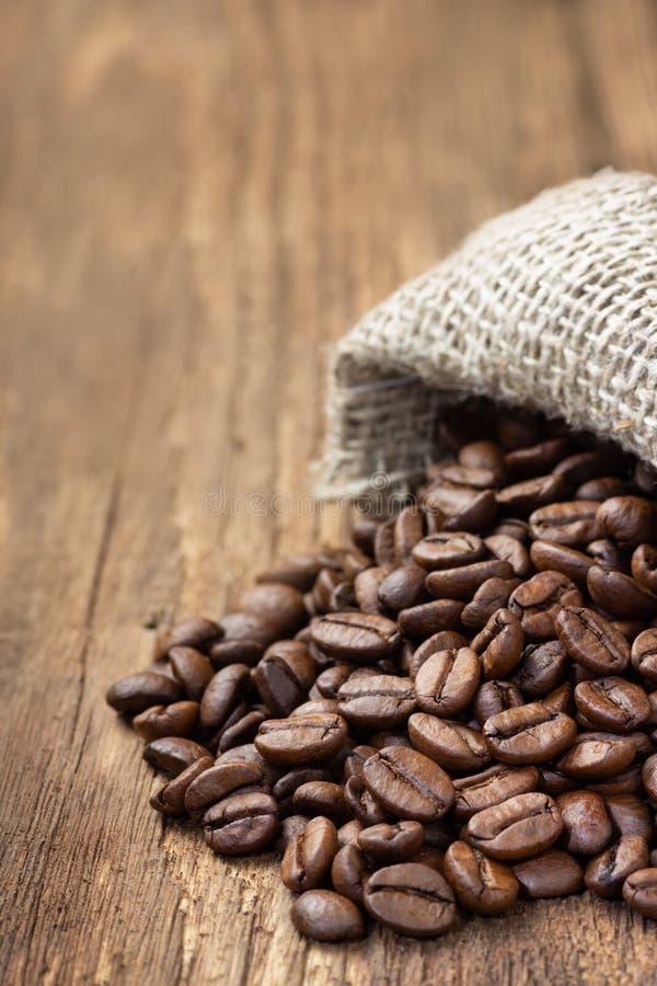 Grains de café dans le sac de toile de jute sur la table en bois photographie stock libre de droits