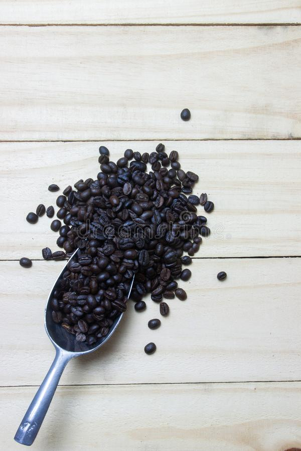 Grains de café dans le scoop sur le fond en bois image stock