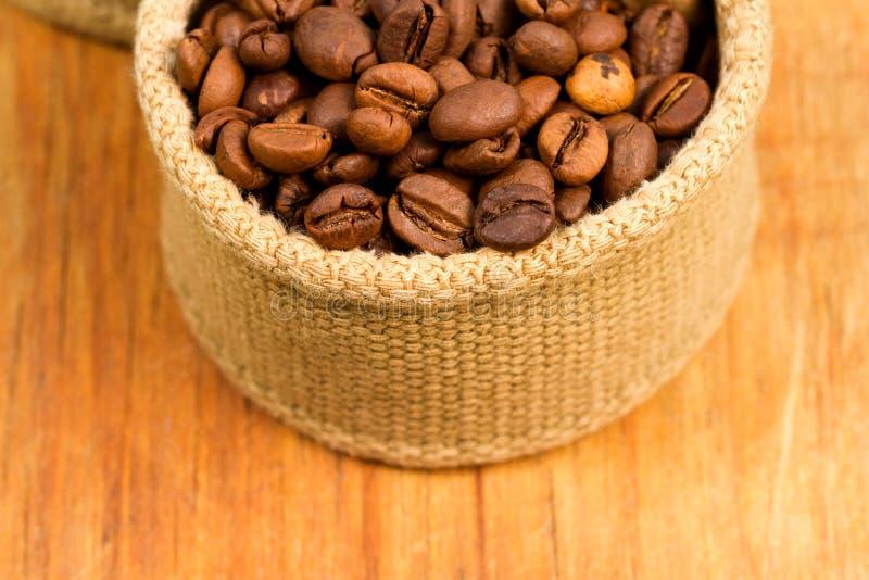 Grains de café dans le tissu sur un en bois photo libre de droits