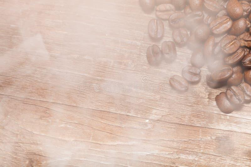 Grains de café dans une fumée sur une vieille table en bois pour le fond images libres de droits