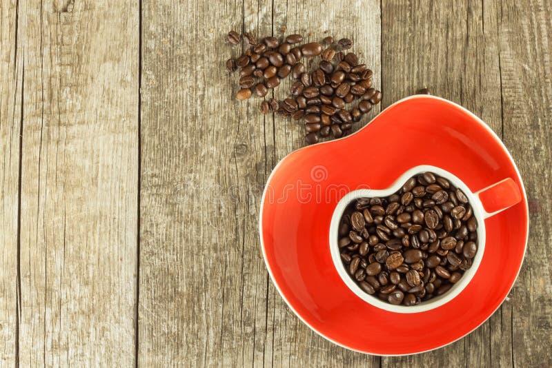 Grains de café dans une tasse Café renversé sur une table en bois Ventes de café frais photos libres de droits