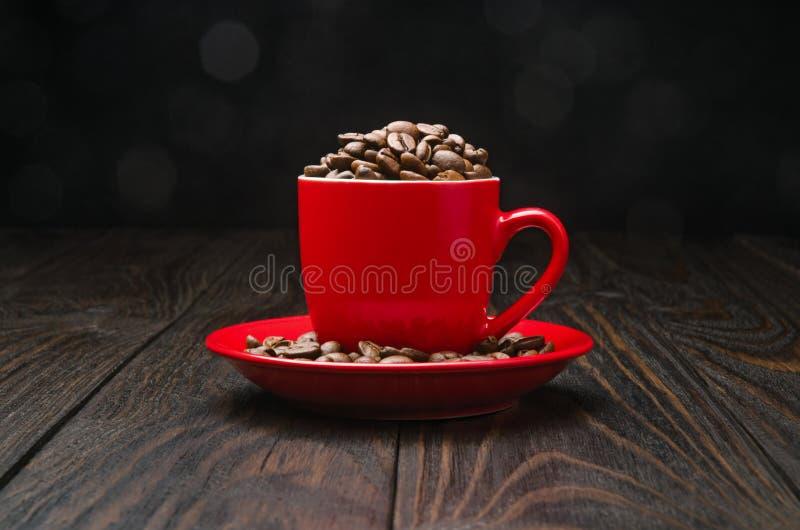 Grains de café dans une tasse rouge photographie stock libre de droits