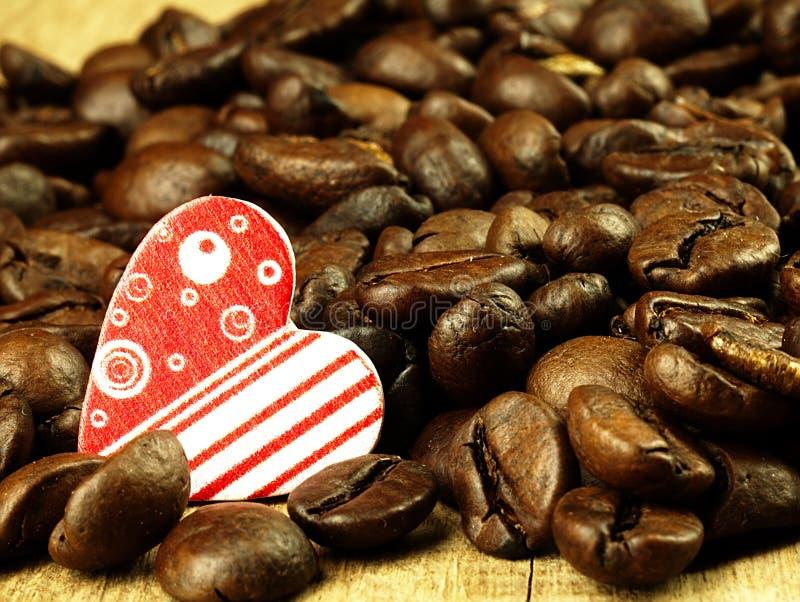Grains de café de coeur et en gros plan sur en bois, table de chêne image libre de droits
