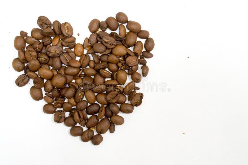 Grains de café en forme de coeur d'isolement sur le blanc photos stock