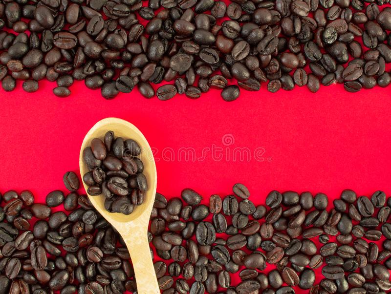 Grains de café en gros plan sur un fond rouge et dans une cuillère en bois photos libres de droits
