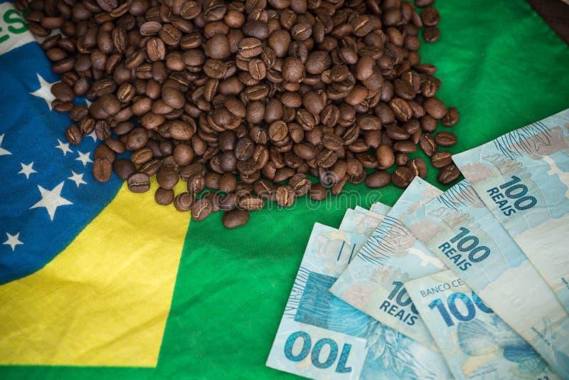 Grains de café et argent brésilien sur le drapeau du Brésil photo stock