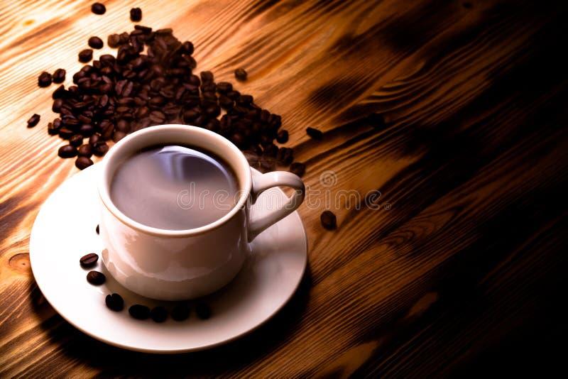 Grains de café et café dans la tasse blanche sur la table en bois sélecteur images stock