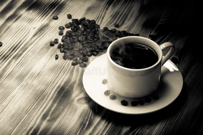 Grains de café et café dans la tasse blanche sur la table en bois sélecteur photo stock
