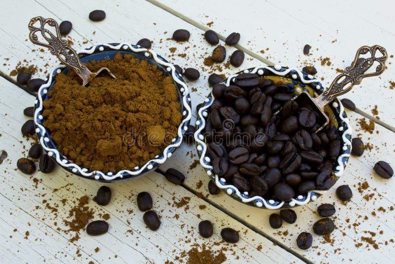 Grains de café et café grinded dans la cuvette sur le fond blanc en bois photo stock