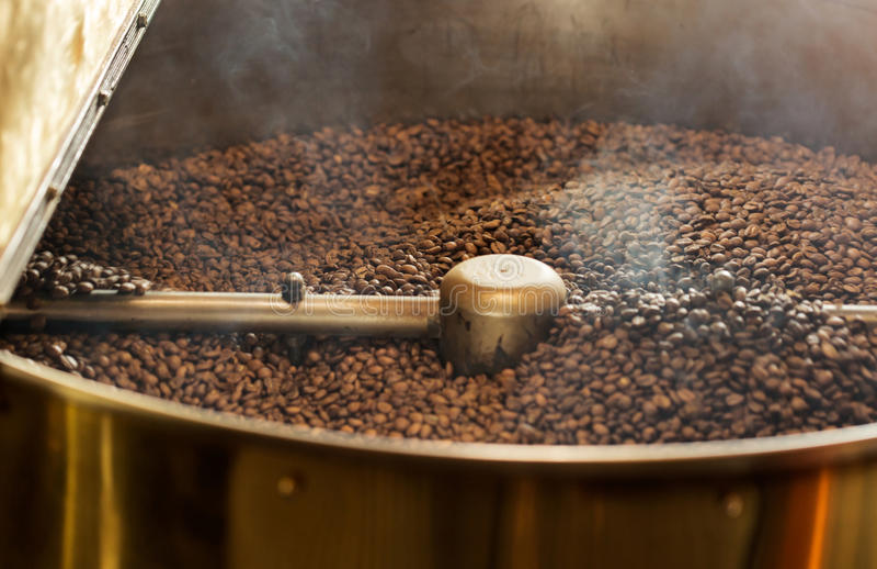 Grains de café foncés dans la machine professionnelle de torréfaction images libres de droits