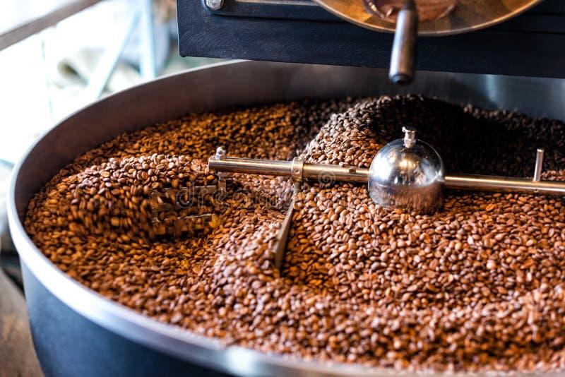 Grains de café fraîchement rôtis d'une grande rôtissoire dans le cylindre de refroidissement Tache floue de mouvement sur des har photos stock