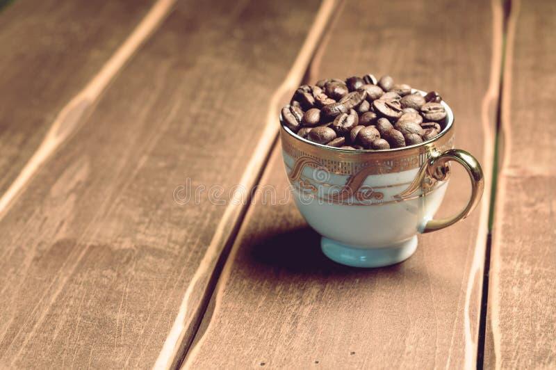Grains de café frais tasse sur un fond en bois photos libres de droits