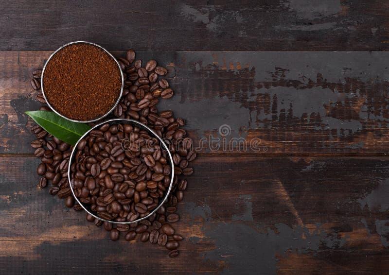 Grains de café organiques crus frais avec la poudre et la feuille moulues de caféier sur le fond en bois photographie stock libre de droits