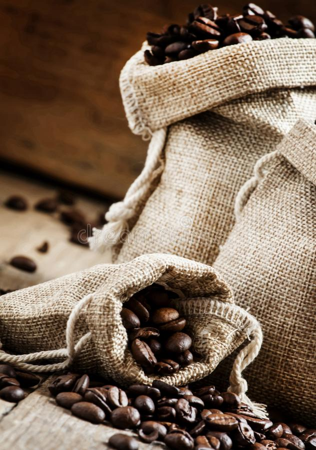 Grains de café rôti dans les sacs sur la vieille table en bois dans s rustique photo libre de droits