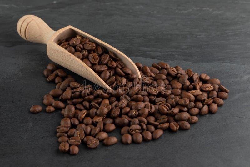 Grains de café rôtis débordant un scoop en bois photos stock