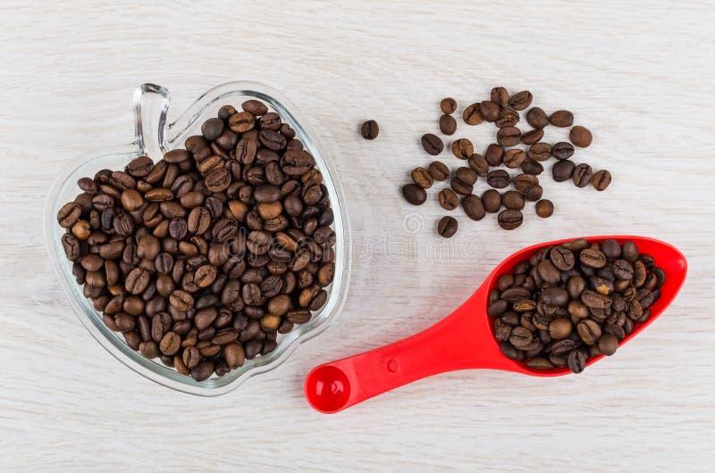 Grains de café rôtis dans la cuillère, dans la cuvette, sur la table en bois photo libre de droits