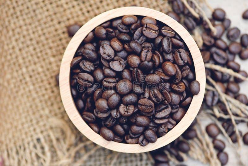 Grains de café rôtis dans le macro de plan rapproché de fond de sac des grains de café sur la cuvette en bois - vue supérieu image libre de droits