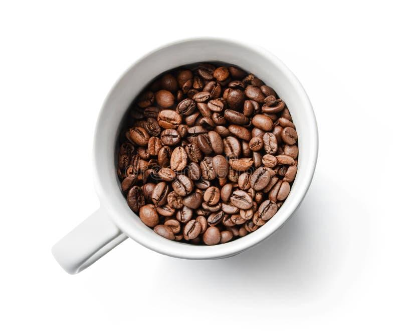 Grains de café rôtis dans une tasse blanche Plan rapproché Fond d'isolement par blanc image libre de droits