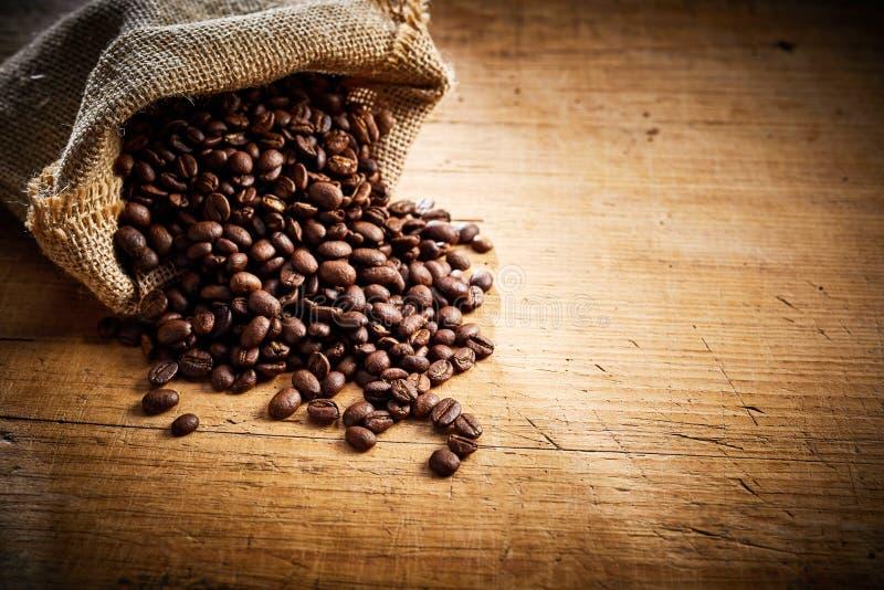 Grains de café rôtis frais débordant un sac photos stock