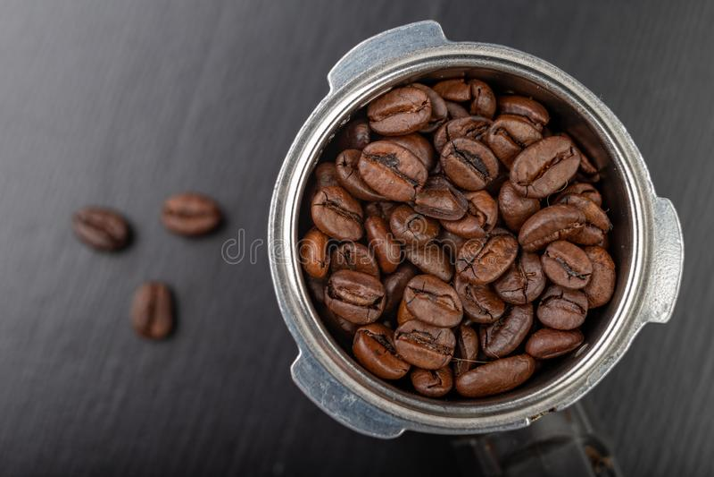 Grains de café rôtis noirs et un flacon de machine de café Accessoires pour le café de brassage sur une table de cuisine noire photo libre de droits