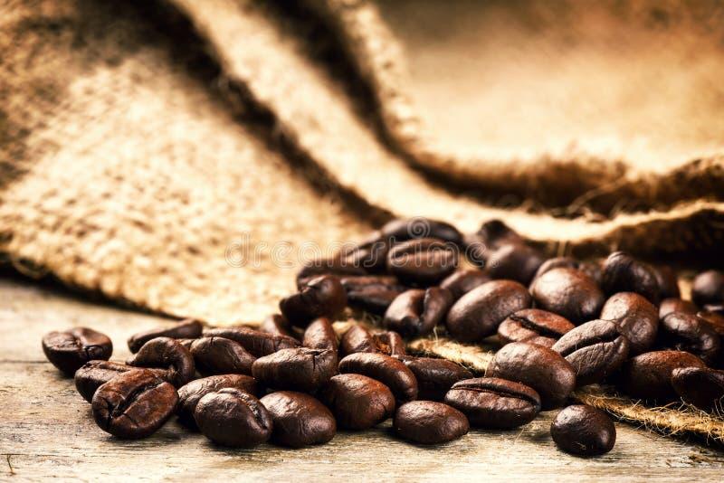 grains de café rôtis sur le vieux fond en bois photos libres de droits