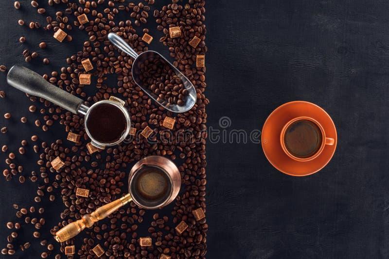 Grains de café, scoop, pot de café, bourreur de café et tasse de café rôtis sur le noir photos libres de droits