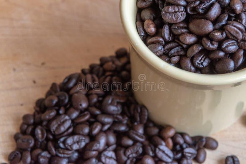 Grains de café se renversant hors de la tasse sur le fond en bois image stock