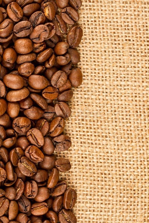 Grains de café sur la toile de jute photographie stock libre de droits