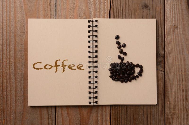 Grains de café sur le carnet ouvert photographie stock libre de droits