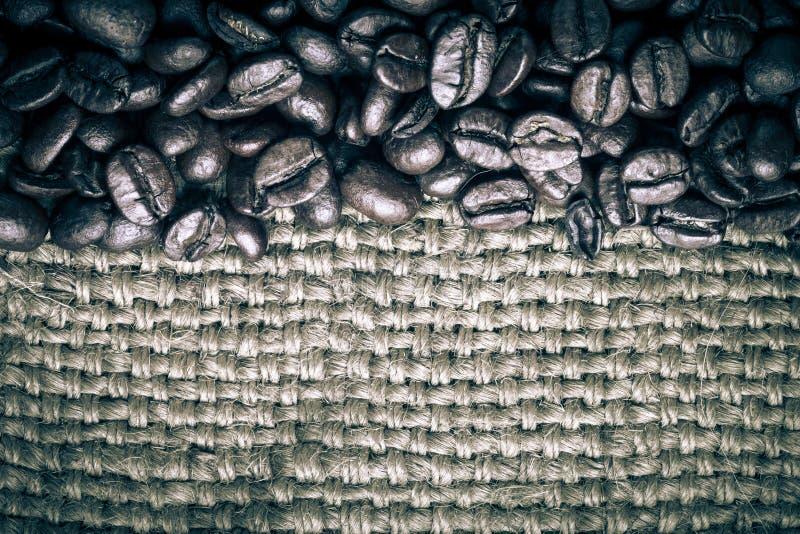 Grains de café sur le fond de toile à sac teinté photo stock