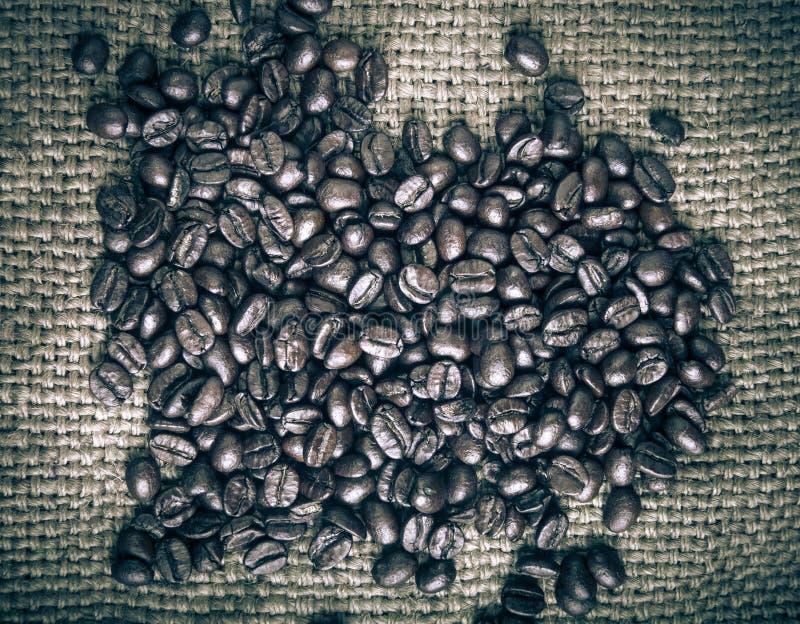 Grains de café sur le fond de toile à sac teinté photo libre de droits