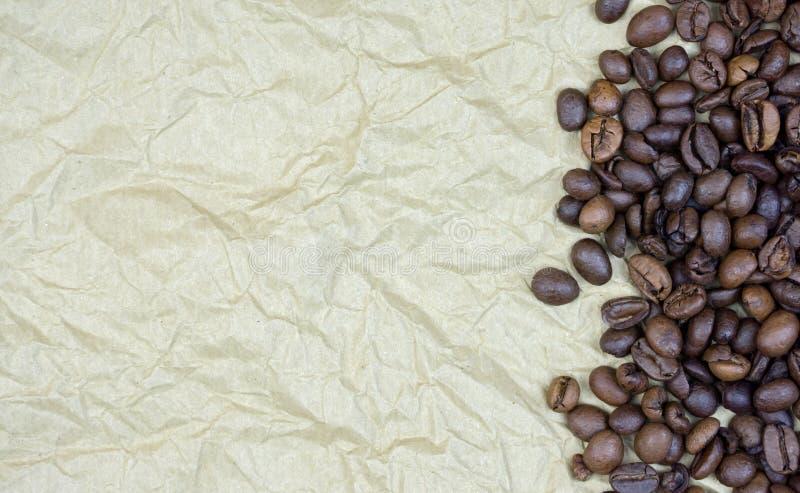 Grains de café sur le vieux papier parcheminé froissé, horizontal photo libre de droits