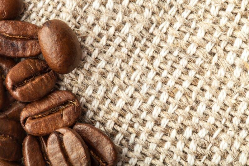 Grains de café sur une serviette légère pour le fond images stock