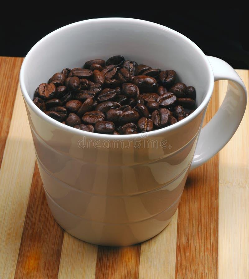 Grains de café sur une tasse photo stock
