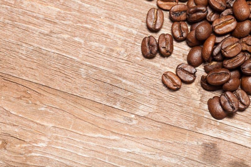Grains de café sur une vieille table en bois pour le fond L'espace pour le tex photographie stock