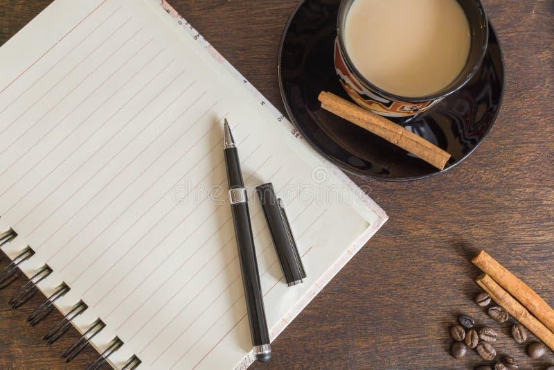 Grains de café, tasse de café, feuilles d'automne, stylo et carnet sur la plate-forme en bois images libres de droits