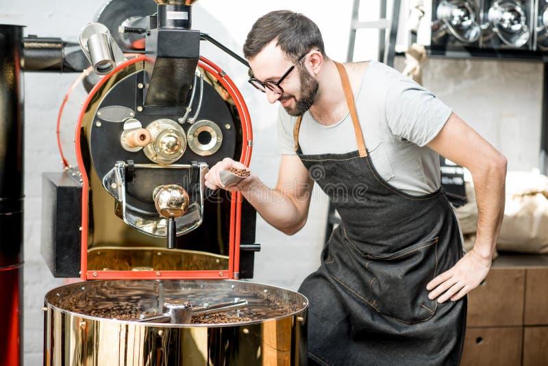 Grains de café de torréfaction d'homme photos stock