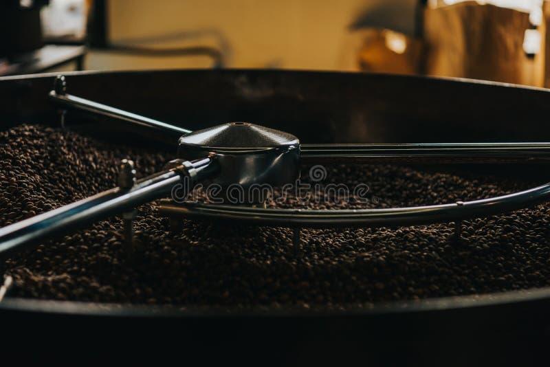 Grains de café de torréfaction dans grand image stock