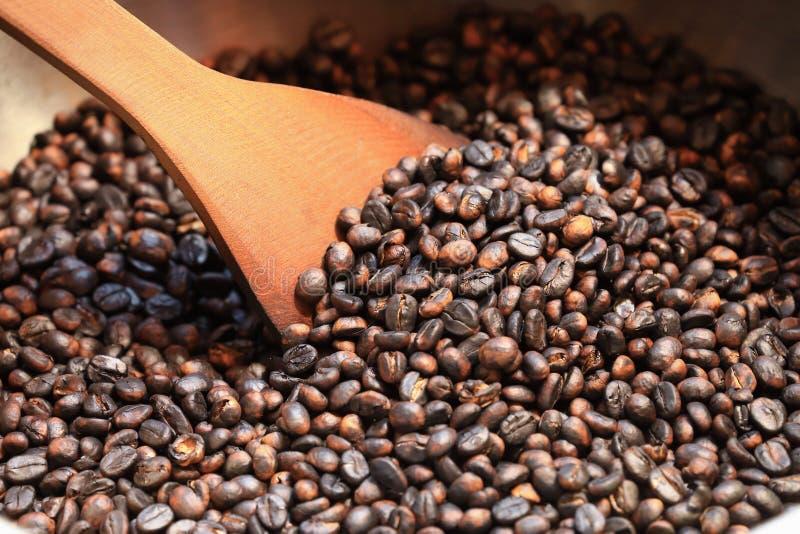 Grains de café traditionnels rôtissant en bassin en métal avec la spatule image stock