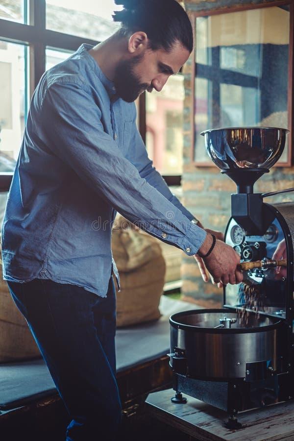 Grains de café de versement d'homme qu'il a rôtis image libre de droits