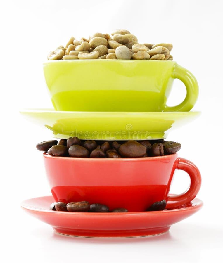 Grains de café verts et noirs dans la tasse images stock