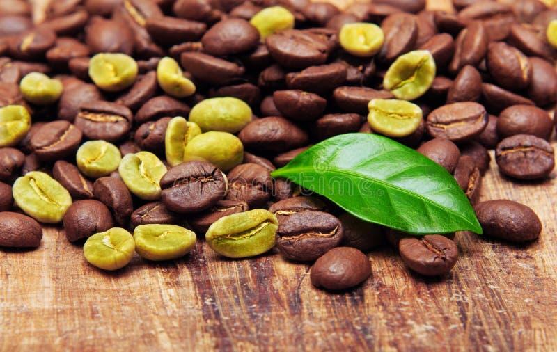 Grains de café verts sur le fond en bois. images stock