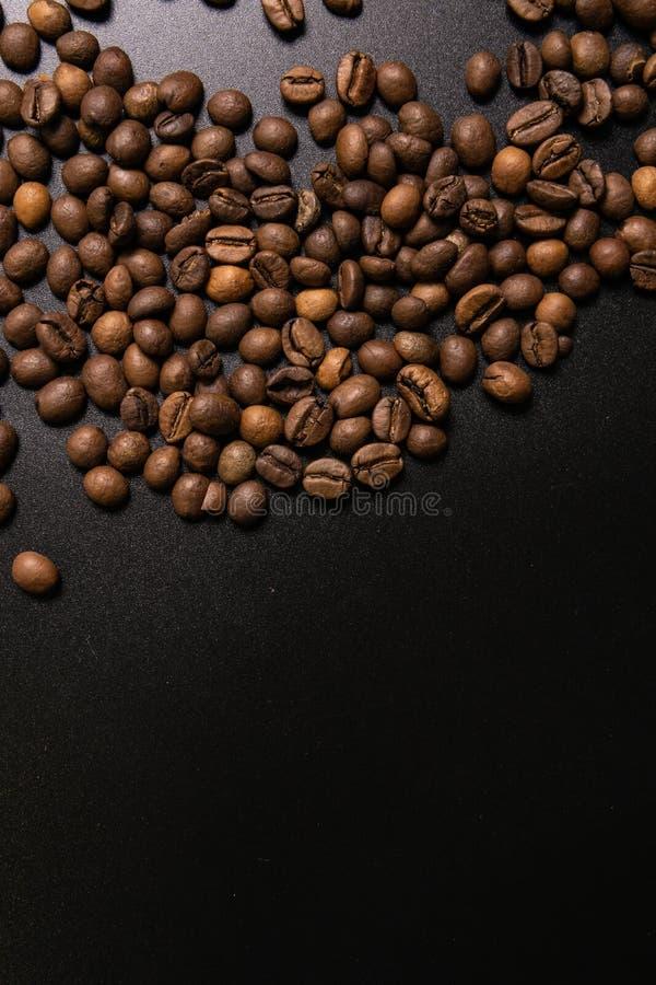 Grains de caf? r?tis en vrac sur un fond noir le cofee fonc? a r?ti le caf? d'arome de saveur de grain, fond naturel de magasin d photographie stock