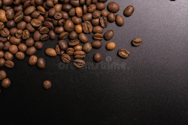 Grains de caf? r?tis en vrac sur un fond noir le cofee fonc? a r?ti le caf? d'arome de saveur de grain, fond naturel de magasin d photo stock