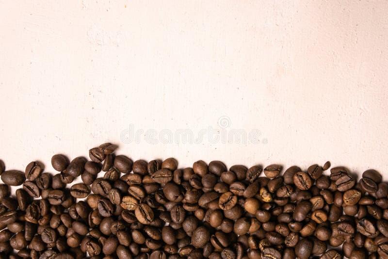 Grains de caf? r?tis en vrac sur un fond rose-clair le cofee fonc? a r?ti le caf? d'arome de saveur de grain, fond naturel de mag image libre de droits