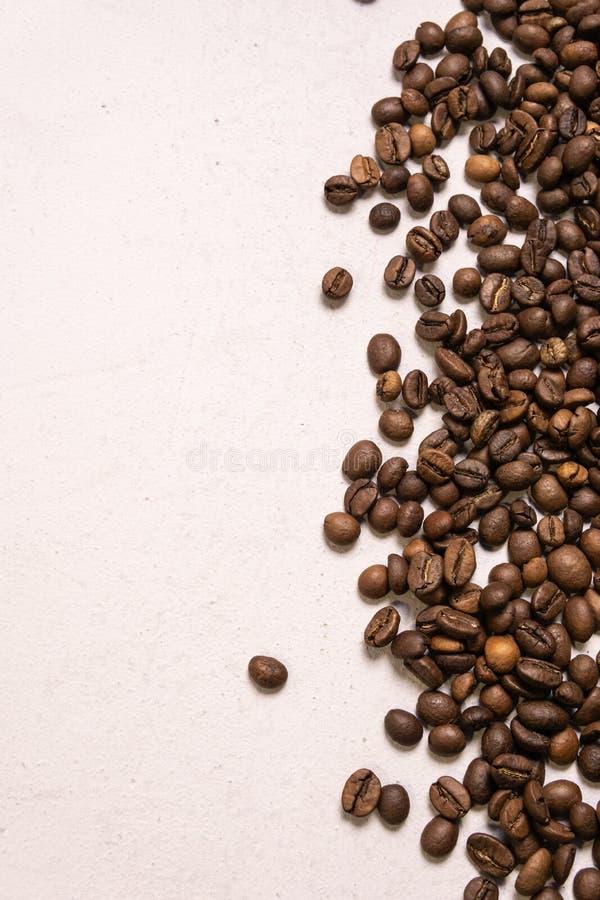 Grains de caf? r?tis en vrac sur un fond rose-clair le cofee fonc? a r?ti le caf? d'arome de saveur de grain, fond naturel de mag photos stock