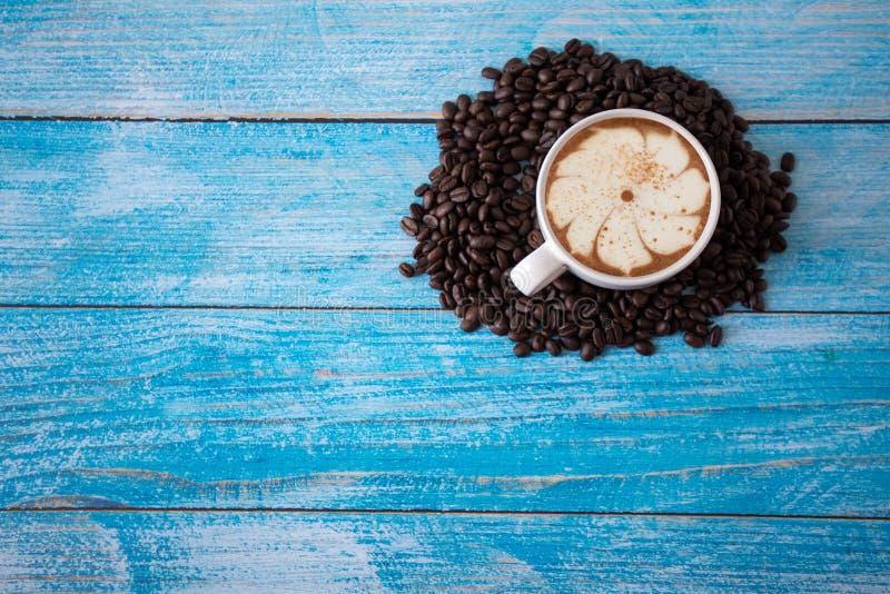 Grains de caf? r?tis plac?s sur un vieux plancher en bois bleu, tasse de caf? de vue sup?rieure pour le fond, concept : petit d?j photos libres de droits