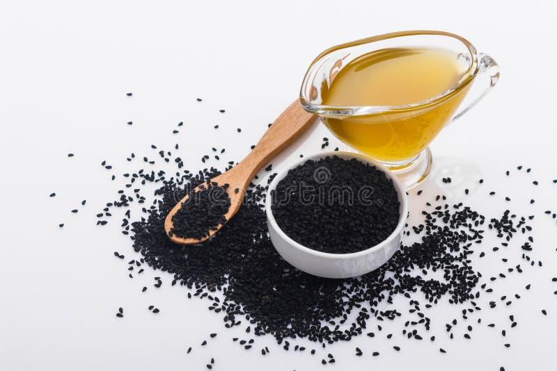 Grains de cumin et de pétrole noirs sur le fond rustique images libres de droits