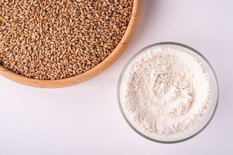 Grains de graines de blé dans la cuvette en bois proche avec la farine de blé dans le bol en verre, vue supérieure, configuration photos stock