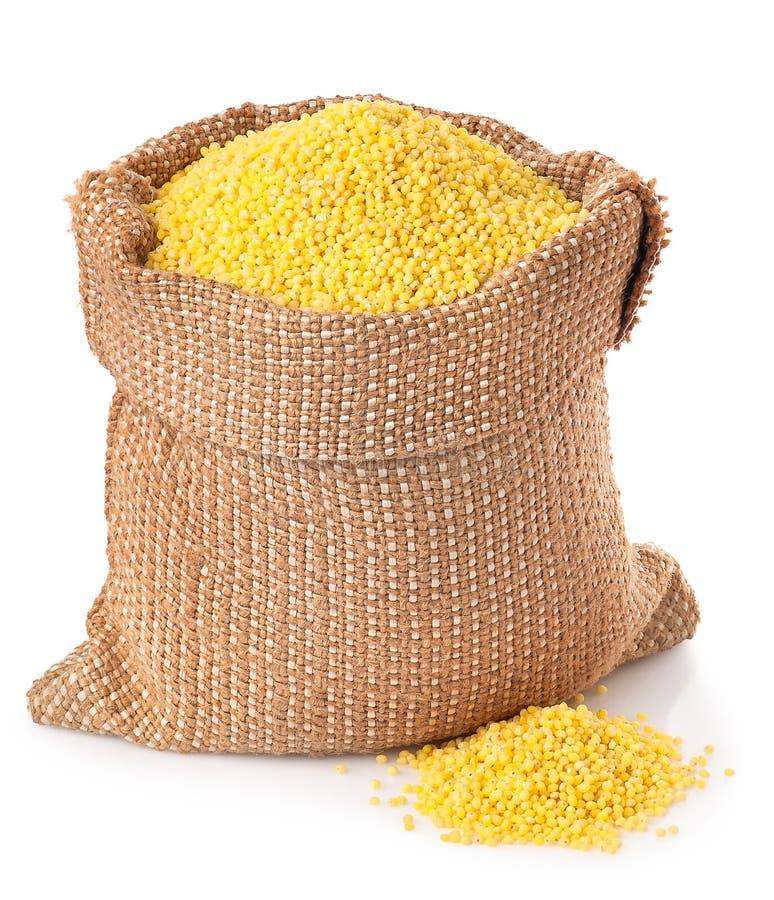 Grains de millet dans le sac d'isolement sur le fond blanc photo stock